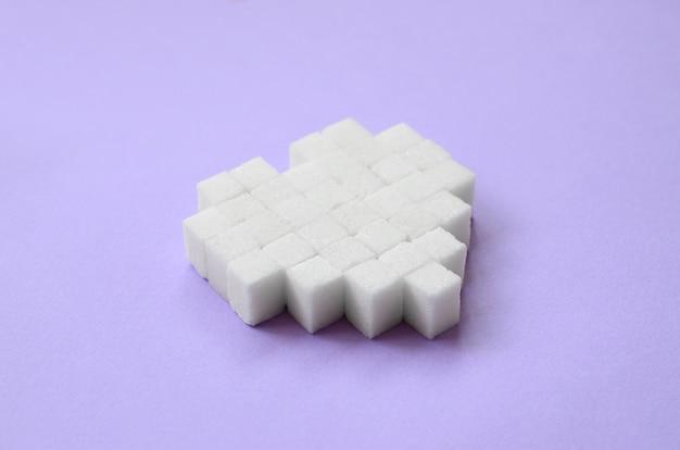 砂糖の立方体で作られた心はトレンディなパステル調の紫色の背景にあります