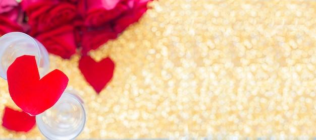 На двух бокалах лежит сердце из лепестков роз, внизу расплывчатый букет из красных роз и ...