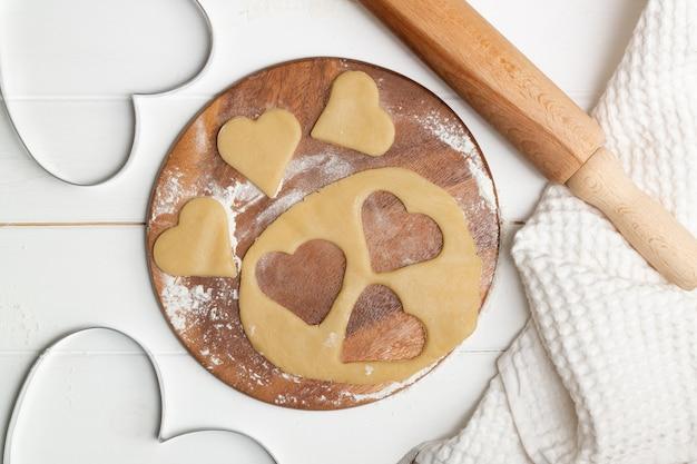 Форма для вырезок в форме сердца и вырезанное из теста печенье рядом с полотенцем, деревянными ложками и скалкой, плоская форма.