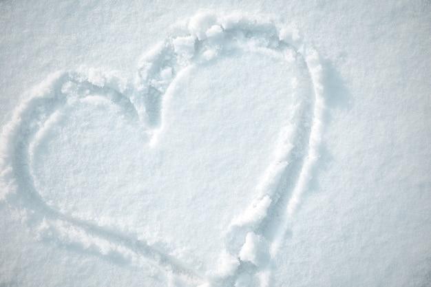 Знак сердца, нарисованный на снегу. вид сверху. конец дня святого валентина. копировать пространство