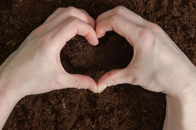 바닥에 하트 모양의 손. 지구의 날. 지구 행성.