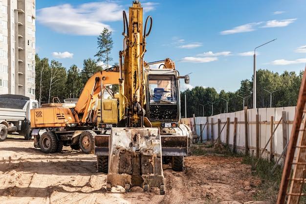 大きなバケツを備えた重いクローラーショベルは、建設中のパネルハウスの前で作業の準備をしています..土工用の重い建設機械。採石場の掘削機。