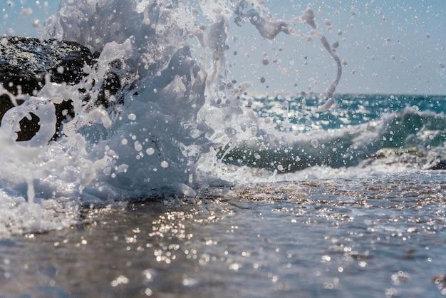 重い海の波が岸に白い泡のしぶきに割り込む