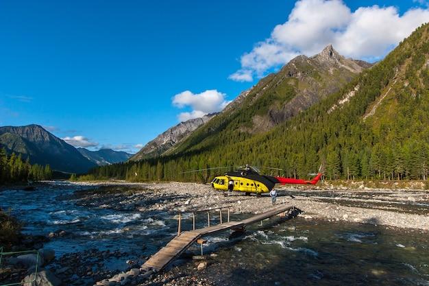 Вертолет стоит у горной реки. через реку проложен мост. мужчина идет к мосту. высокие горы засажены деревьями за вертолетом. облака на голубом небе. по горизонтали.