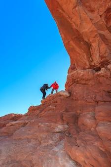 바위를 등반하는 여성에게 도움의 손길 arches national park usa