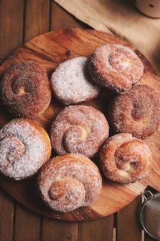 Снимок восхитительных пончиков со змеями, покрытых сахарной пудрой, под большим углом