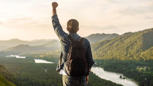 배낭을 든 등산객 남자가 산 정상에 손을 들고 승자의 포즈를 취합니다. 여행 및 휴가 개념. 트레킹 또는 승리