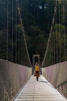 ラローのホルツァルテ吊橋を渡る黄色いバックパックを持ったハイカー。ピレネー・アトランティックスのイラティの森やジャングルで