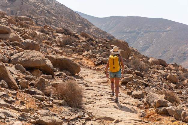 노란색 배낭을 메고 카나리아 제도 푸에르테벤투라의 mirador de la peñitas를 향해 협곡 길을 걷고 있는 등산객. 스페인