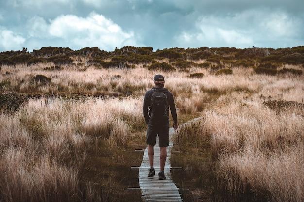 Пеший человек идет по тропе с желтой травой на высокой горе. облачно и дождь сцена.