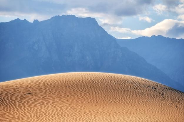 Холм в пустыне северного мира с волнистым узором, освещенный солнцем на фоне затемненного горного хребта кодар.