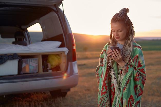 明るい毛布に身を包んだヒッピーの女の子とドレッドヘアが車の近くの畑でコーヒーを飲んでいる...