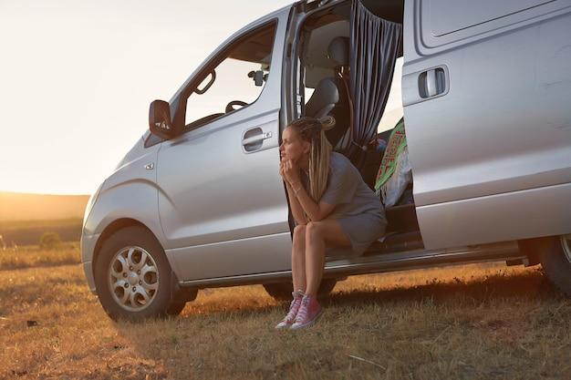 ヒッピーの女の子がミニバンに座って、出て行く太陽を背景にドアを開けて...