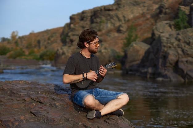 안경을 쓴 히피 남자가 산의 강가에 앉아 우쿨렐레를 연주합니다.