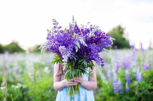 野生の花の花束を手に持ったヒッピーの女の子。女の子はルピナスの花束の後ろに顔を隠しました。小さな女の子は、開花フィールドに紫のルピナスの大きな花束を保持しています。自然のコンセプト。プレゼント