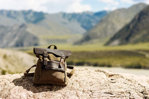 流行に敏感な茶色のトラベルバックパック。山を背景にバッグの正面からの眺め。休暇中の旅行者、テキスト用の空白のぼやけたモックアップ