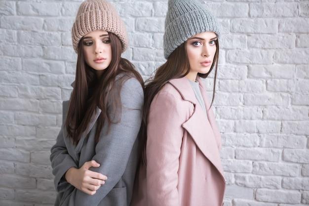 スタイリッシュなコートとニット帽を身に着けている長い茶色の髪の流行に敏感なカジュアルな女の子は、通りの明るい白のレンガの背景に立っている間脇を見ています。水平モックアップ。