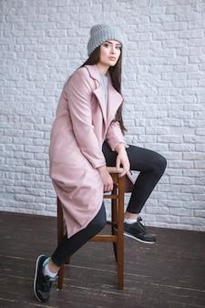 スタイリッシュなコートとニット帽を身に着けている長い茶色の髪の流行に敏感な女の子は、通りの明るい白のレンガの背景に立っている間、脇を見ています。水平モックアップ。