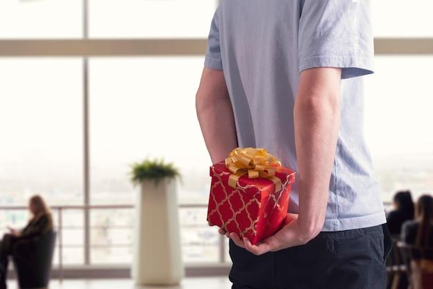 Держит подарочную коробку за спиной мужчине - сюрприз