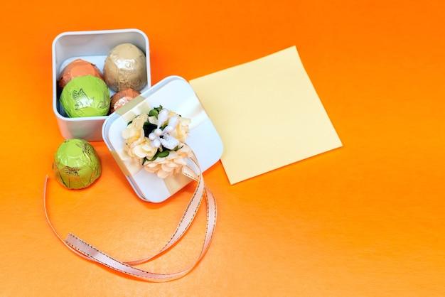 おめでとうのメモ付きのホリデーギフト。お菓子のギフト包装。オレンジ色の背景。セレクティブフォーカス