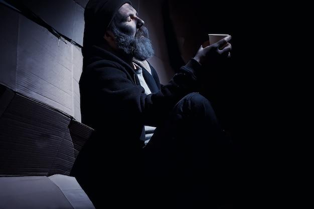 Бездомный бородач сидит на ящиках на улице и просит о помощи. нужен бомж, просит денег на еду и ночлег.