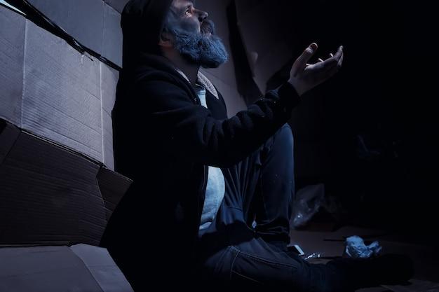 수염 난 노숙자가 거리의 상자 위에 앉아 도움을 요청합니다. 노숙자가 음식과 하룻밤에 돈을 요구합니다.