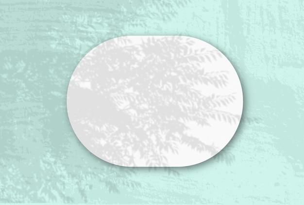 Горизонтальный овальный лист белой фактурной бумаги на синей стене