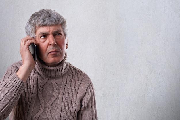 携帯電話で話している深刻な、心配している、動揺している成熟した男の水平方向の肖像画。電話でいくつかの問題を決定する古い従業員
