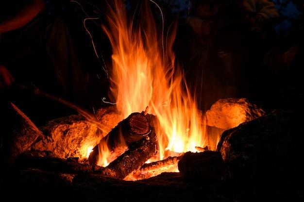 黒の背景の夏のロマンチックな休日の夜のホットキャンプファイヤー