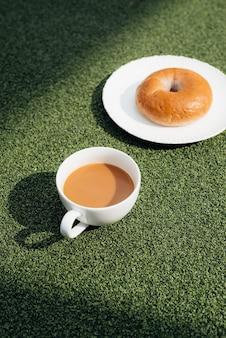 이슬 배경이 있는 푸른 잔디에 있는 추운 아침에 뜨거운 커피와 도넛