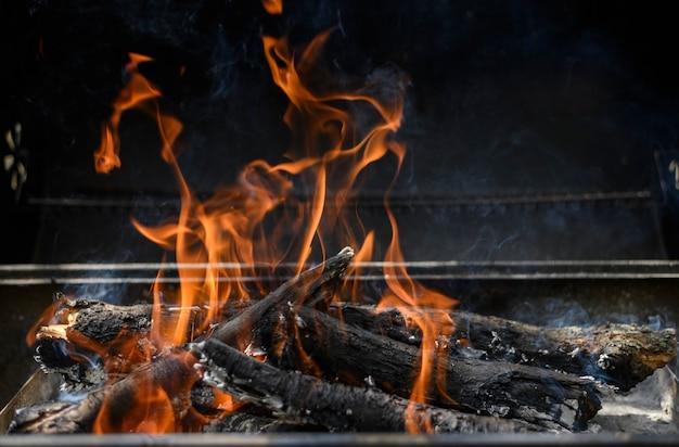 黒の背景の夏のバーベキューのコンセプトでバーベキューの熱い火