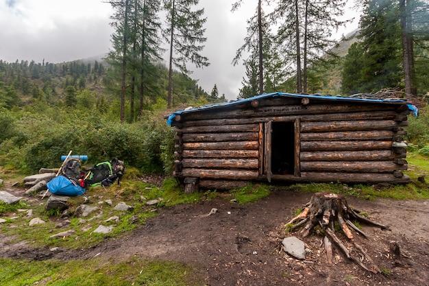 Бревенчатый домик с названием - бегущий олень - в горах для ночевок во время переходов. рядом рюкзаки в куче. горы с лесом в тумане на заднем плане. по горизонтали.