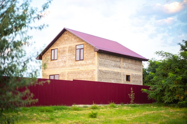 여름이면 마을의 울타리 뒤에 진홍색 지붕이 있는 집. 교외 주택 건설.