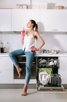 Девушка-домохозяйка в розовых перчатках после уборки в доме усталая сидит на кухне. на белой кухне девушка вымыла посуду и отдыхает. много мытой посуды.