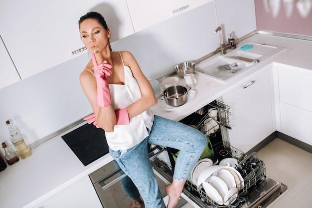 Хозяйка в розовых перчатках после уборки дома усталая сидит на кухне. на белой кухне девушка вымыла посуду и отдыхает. много вымытой посуды.