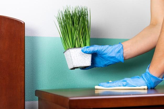 Хозяйка в рубашке убирается в доме, вытирает пыль со стола тряпкой для уборки.