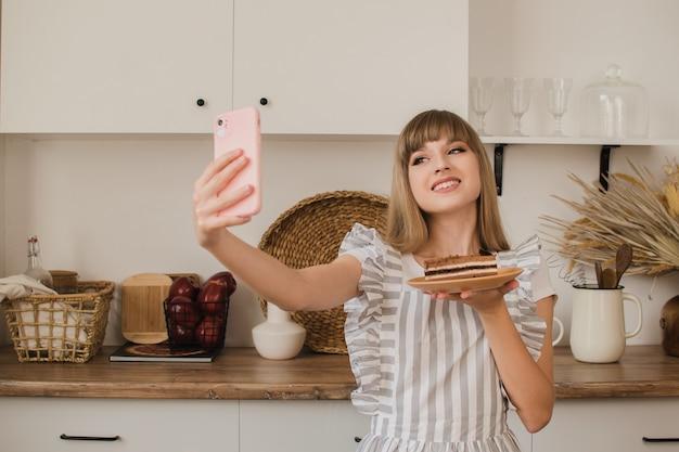 Домохозяйка или кондитер делает селфи с десертом. блог о еде. кулинарные курсы. девушка-блогер