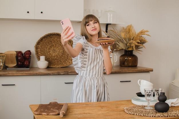주부나 제빵사가 디저트와 함께 셀카를 찍는다. 음식 블로그. 요리 코스. 블로거 소녀