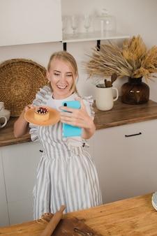 주부나 제빵사가 디저트와 함께 셀카를 찍는다. 음식 블로그. 요리 코스. 블로거 여성
