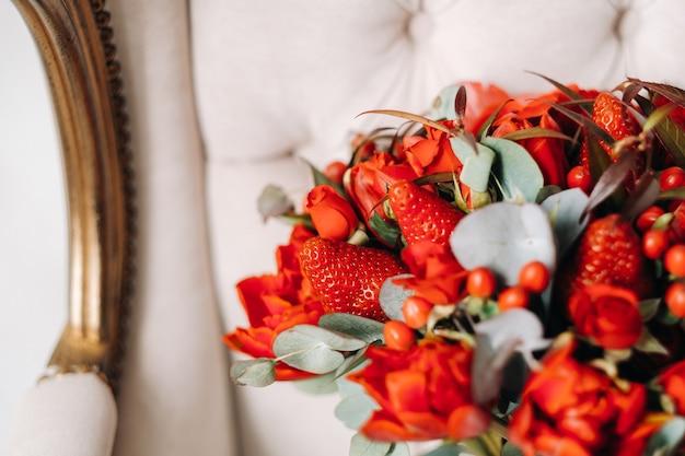 딸기와 함께 아름다운 빨간 장미의 거대한 꽃다발이 의자에 놓여 있습니다