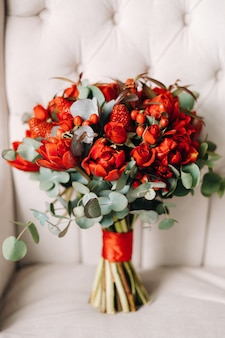 На стуле лежит огромный букет красивых красных роз с клубникой.