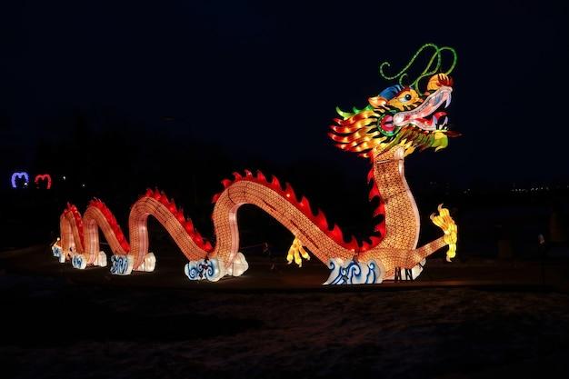 Огромный яркий светящийся китайский дракон лунь во время празднования китайского нового года на фестивале китайских фонарей