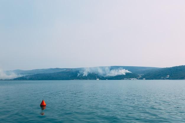 Огромный столб дыма распространяется по полуострову луштица в черногории, недалеко от города крашичи. фото высокого качества