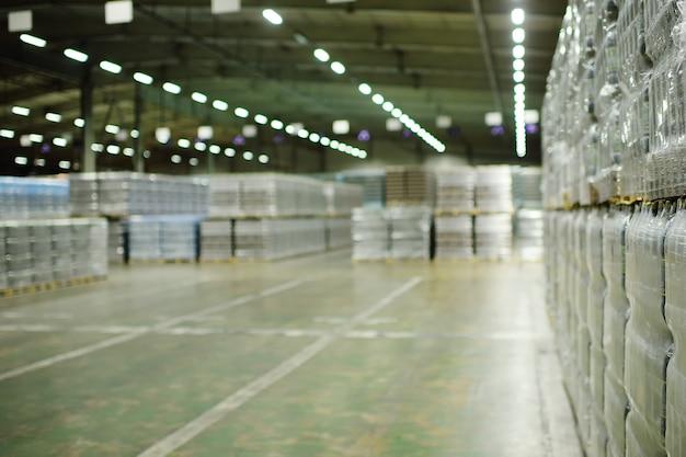 炭酸飲料、水、またはビールでラップされたペットボトルを備えた巨大な産業倉庫。