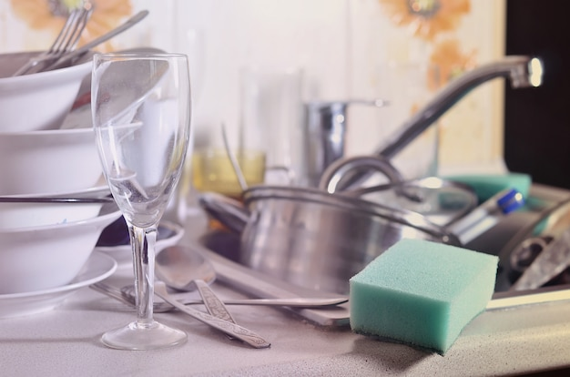 Огромная куча немытой посуды в кухонной раковине и на столешнице