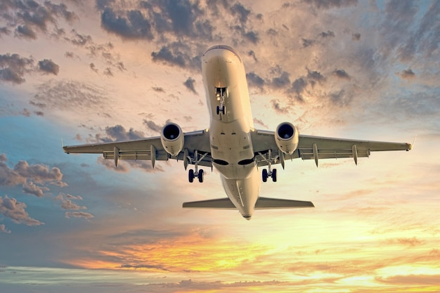夕焼けの空を背景に飛行中の巨大な飛行機