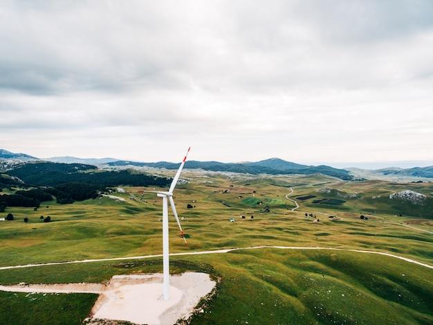 Огромная ветряная электростанция с тремя лопастями на зеленых холмах в черногории