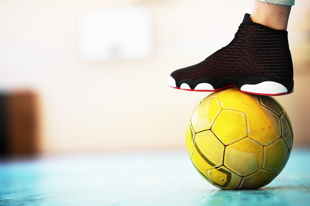 Человеческая нога упирается в футбольный мяч на бетонном полу. фотография одного футбольного мяча и кроссовок на деревянном полу.