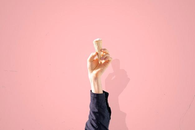 カラーパステル背景、抽象的な創造的なアイデアに分離されたアイスクリームコーンを保持している人間の手