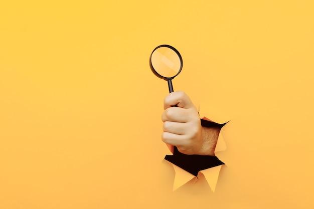 인간의 손은 종이 노란색 벽에 찢어진 구멍을 통해 돋보기를 보유하고 있습니다.